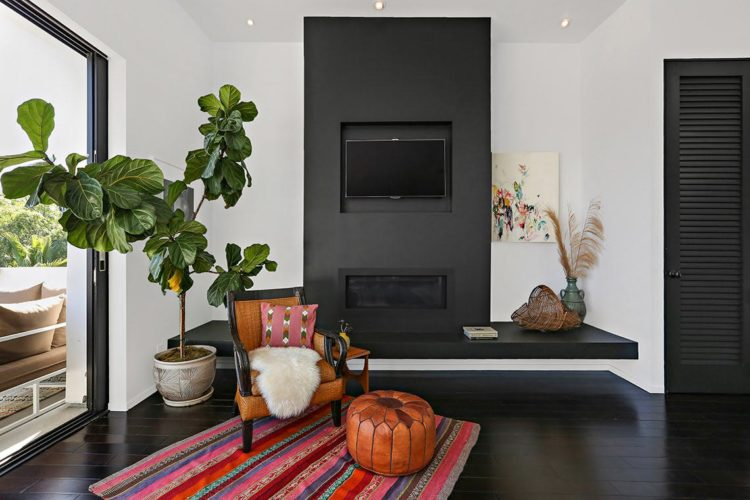 black fire place and fiddle leaf fig