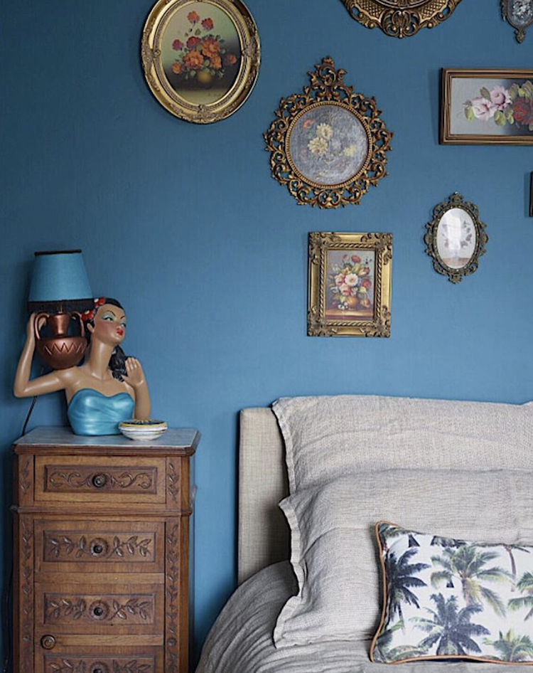 The antique wooden bedside table sits within a modern bedroom with a bright blue wall, kitsch table lamp and a gallery wall of traditional frames. KAte Watson-Smyth looks at ways of introducing brown or rather antique furniture into a scheme. #antiquefurniture #gallerywall #katewatsonsmyth