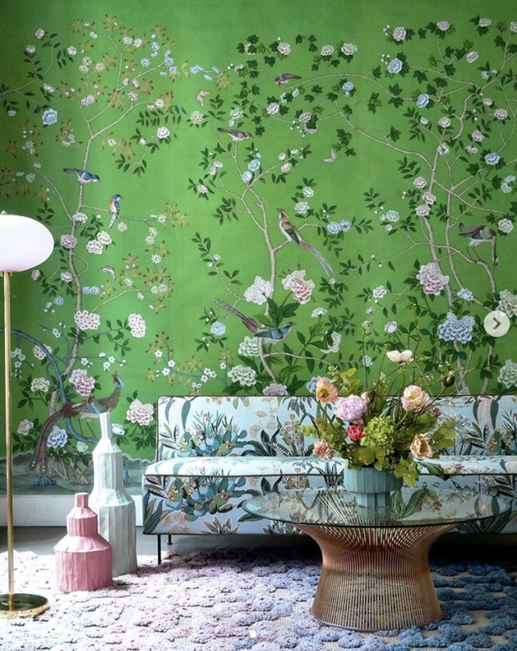 Emerald green Chinoiserie wallpaper by de Gournay with floral sofa, textured rug and glass coffee table.