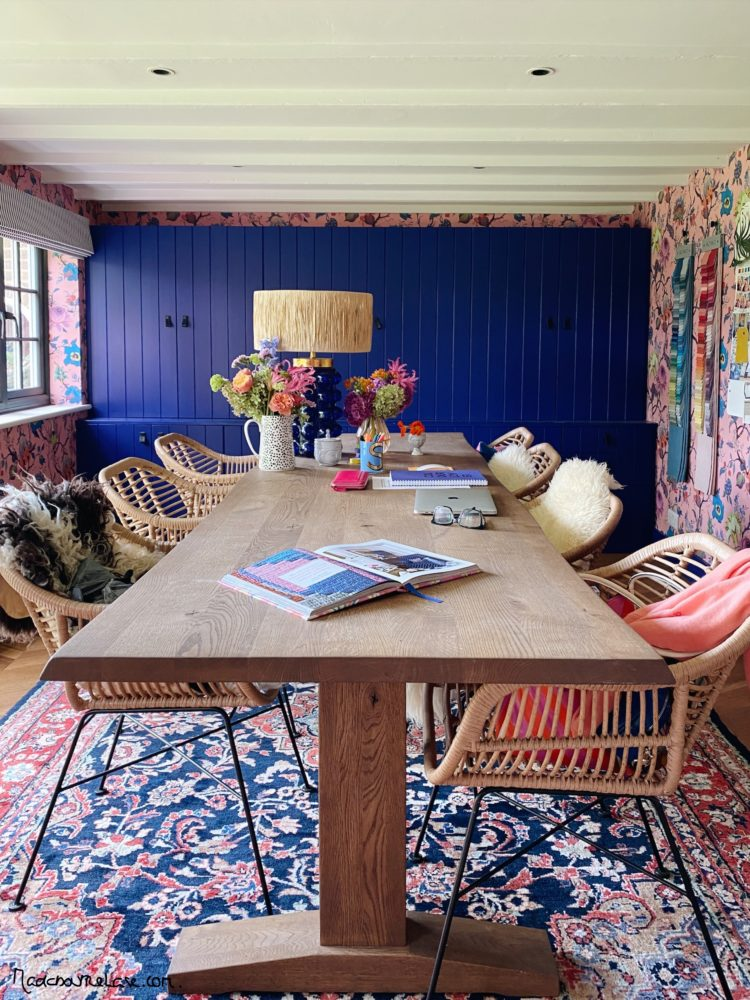 Large wooden dining table, rattan chairs, cobalt blue painted cupboards, large patterned rug in the home office of Sophie Robinson