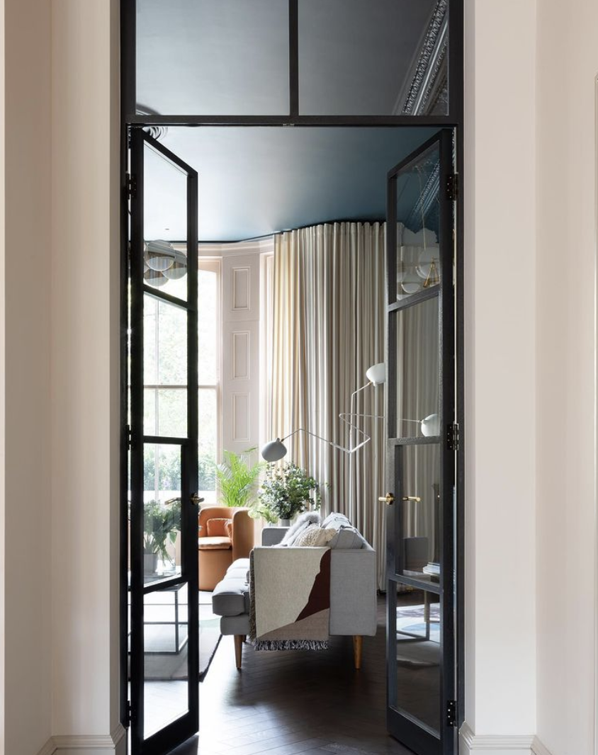 internal black framed glass doors through to living room with soft neutral tones. by frank & faber