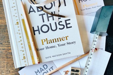 Mad About the House, new book scattered with stationery and tape measure on wooden table.