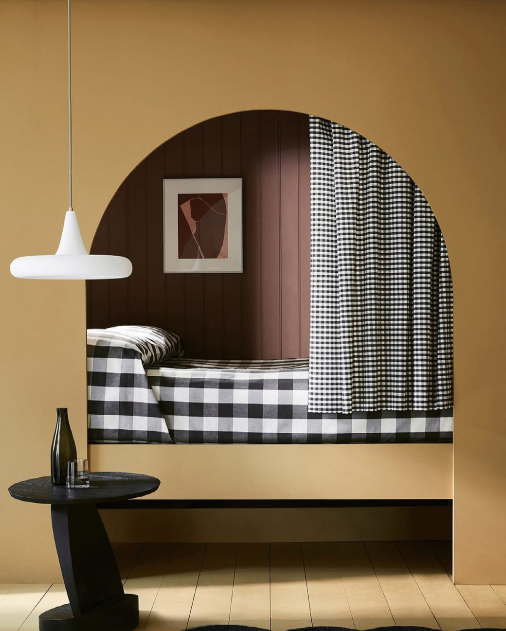 tobacco coloured built in bed with arch and large gingham check bedlinen in black and white.
